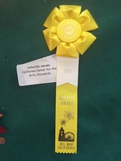 "July 4: Look What I won at the Del Mar Fair! It's a ribbon and award from the California  Center for the Arts in Escondido, CA for my large collage (hundreds of small acrylic painted pieces) acrylic painting: ""Embraced in Wonderland."""